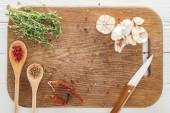 top view of various spices and thyme on wooden chopping board