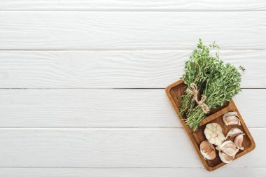 top view of fresh green thyme and garlic cloves on white wooden table