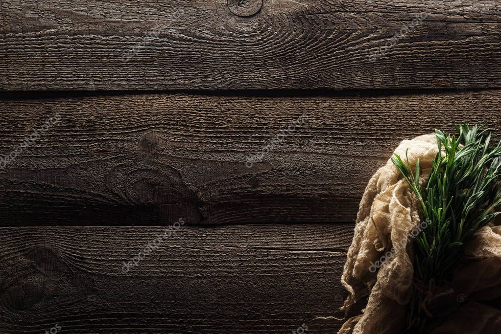 top view of green rosemary in cotton rustic cloth on wooden weathered table with copy space