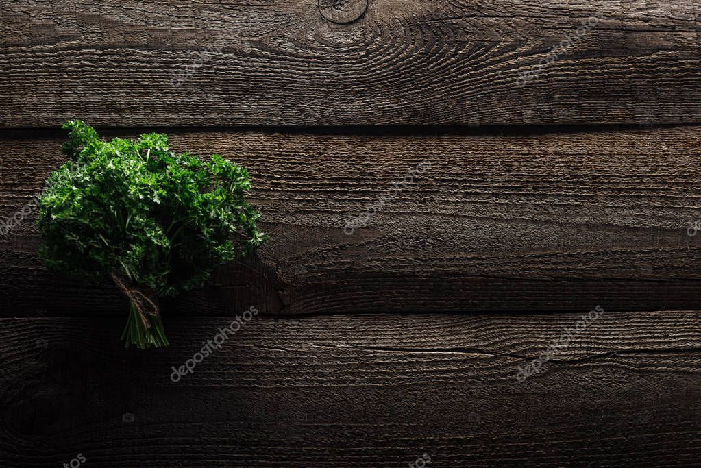 top view of green parsley on wooden weathered table with copy space