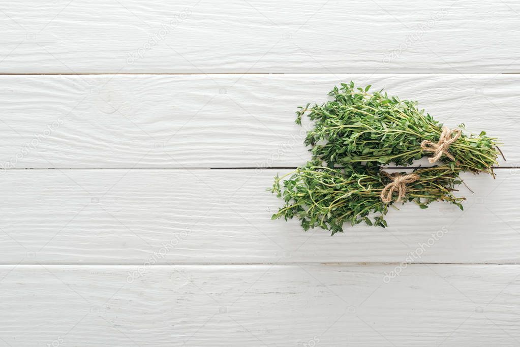 top view of fresh green thyme on white wooden table