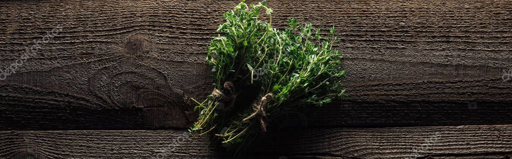 top view of green fresh thyme on wooden brown rustic table, panoramic shot
