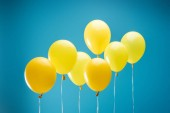 bright colorful yellow balloons on blue background