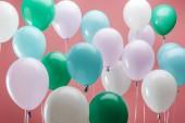světle zelené, bílé a modré ozdobné balónky na růžovém pozadí