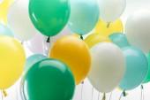 közelről kilátás-ból okos zöld, sárga és kék dekoratív léggömb-ra fehér háttér
