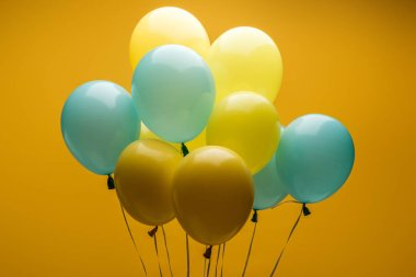 Bright decorative blue and yellow balloons on yellow background stock vector