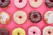 vista superiore di gustosi ciambelle vetrate colorate su sfondo rosa brillante