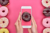 cropped view of woman holding smartphone with doughnut image on pink background near tasty doughnuts