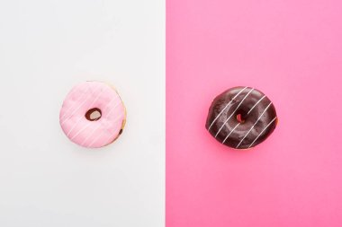 Top view of chocolate and pink glazed doughnuts on pink and white background stock vector
