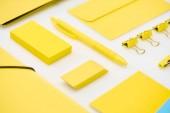 rovné žluté pero, nálepky, papírové sponky, složky, gumy a obálky na bílém pozadí