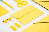 lapos feküdt sárga boríték, ceruza, matricák, olló és gemkapcsok fehér háttér