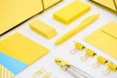 flat lay of yellow paper clips, compasses, envelope, pen, yellow and blue stickers, folders and eraser