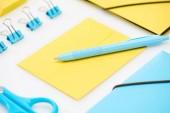 modré nůžky, papírové sponky, složky a pera na žluté obálce v blízkosti žluté složky na bílém pozadí