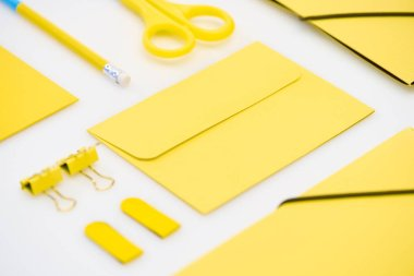 Flat lay of yellow envelope, pencil, stickers, scissors and paper clips on white background stock vector