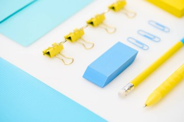 flat lay of blue eraser, paper clips, folder, envelope, yellow pen, pencil, stickers in white background