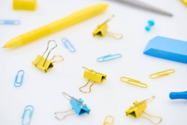 Selective focus of yellow and blue paper clips with pen, eraser, scissors and pencil sharpener on white background stock vector