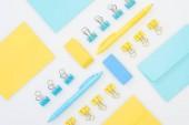 ploché žluté a modré gumy, pera, obálky a kancelářské sponky izolované na bílém