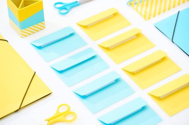 Flat lay of colourful envelopes, scissors, folders, pencil case and pencil box on white background stock vector