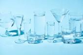 occhiali trasparenti con acqua limpida su sfondo blu