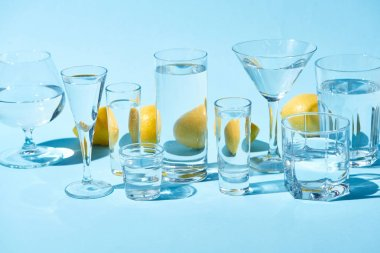 Transparent glasses with water and whole lemons on blue background stock vector