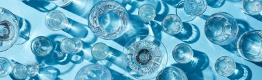 top view of glasses with clear water and shadows on blue surface, panoramic shot