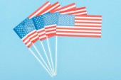 top view of american flags on sticks on blue background