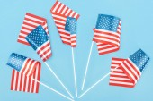 top view of decorative american flags on sticks on blue background