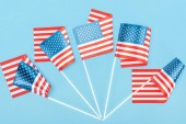 top view of traditional american flags on sticks on blue background