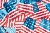 top view of national american flags on sticks scattered on blue background