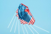 top view of shiny american flags on sticks on blue background