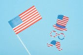 Photo top view of usa flag on stick near paper cut mustache, hat and glasses on blue background