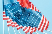 close up view of silk american flags on sticks on blue background