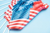 close up view of silk usa flags on sticks on blue background