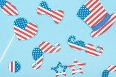 top view of paper cut decorative mustache, glasses, hat and heart made of usa flags on blue background