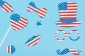 top view of paper cut decorative mustache, glasses, hat, lips and heart made of american flags on blue background