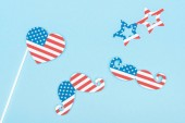 top view of paper cut decorative glasses, mustache and heart made of american flags on blue background
