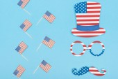 flat lay with hat, glasses and mustache made of stars and stripes near decorative american flags on wooden sticks on blue background