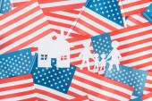 top view of white paper cut house and family on american flags background