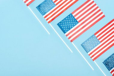 flat lay with american flags on sticks on blue background with copy space
