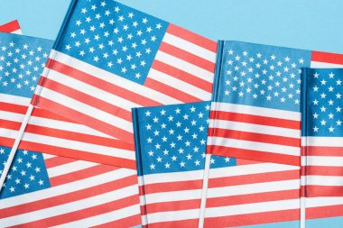 Close up view of decorative american flags on sticks on blue background stock vector