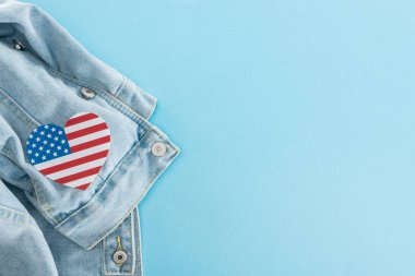Top view of paper cut heart made of american flag on denim stylish jacket on blue background with copy space stock vector