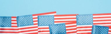 panoramic shot of national patriotic american flags on blue background