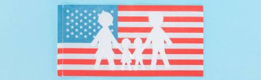 Panoramic shot of paper cut white family on national american flag on blue background stock vector