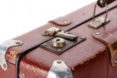 close up view of metal rusty lock on vintage brown suitcase isolated on white