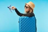 Blondes glückliches Mädchen mit Sonnenbrille und Strohhut mit Spielzeugflugzeug nahe blauer Reisetasche isoliert auf blauem Grund