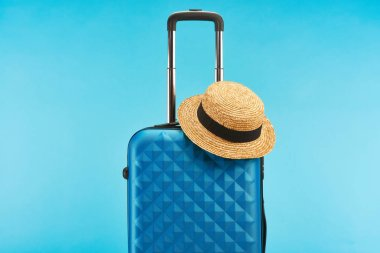 Blue colorful travel bag with handle and straw hat isolated on blue stock vector