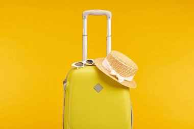 yellow colorful travel bag with sunglasses and straw hat isolated on yellow