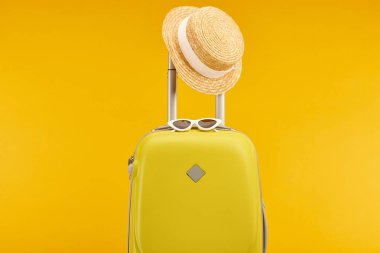 yellow colorful travel bag with sunglasses and straw hat on handle isolated on yellow