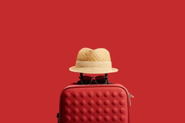 Red travel bag with straw hat and sunglasses isolated on red stock vector