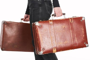 Cropped view of woman in jeans holding vintage weathered suitcases isolated on white stock vector